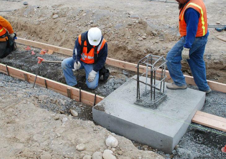 Einzelfundament mit Bauarbeitern